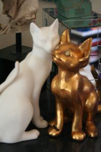 A staue of a white and a golden cat
